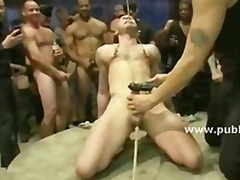 Muscular gay man is immobilized on a spinning platform and has his dick sucked